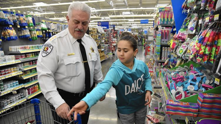 Left, Anthony Scarpelli, Chief of Police of Skokie, shops Dec. 12, 2015 at the Skokie Walmart (3626 Touhy Ave.) with Valentina Aburukbah, 12, of Chicago and a Skokie/Morton Grove MCC Academy fifth-grader during the Cops with Kids shopping holiday program. (Karie Angell Luc / Pioneer Press)